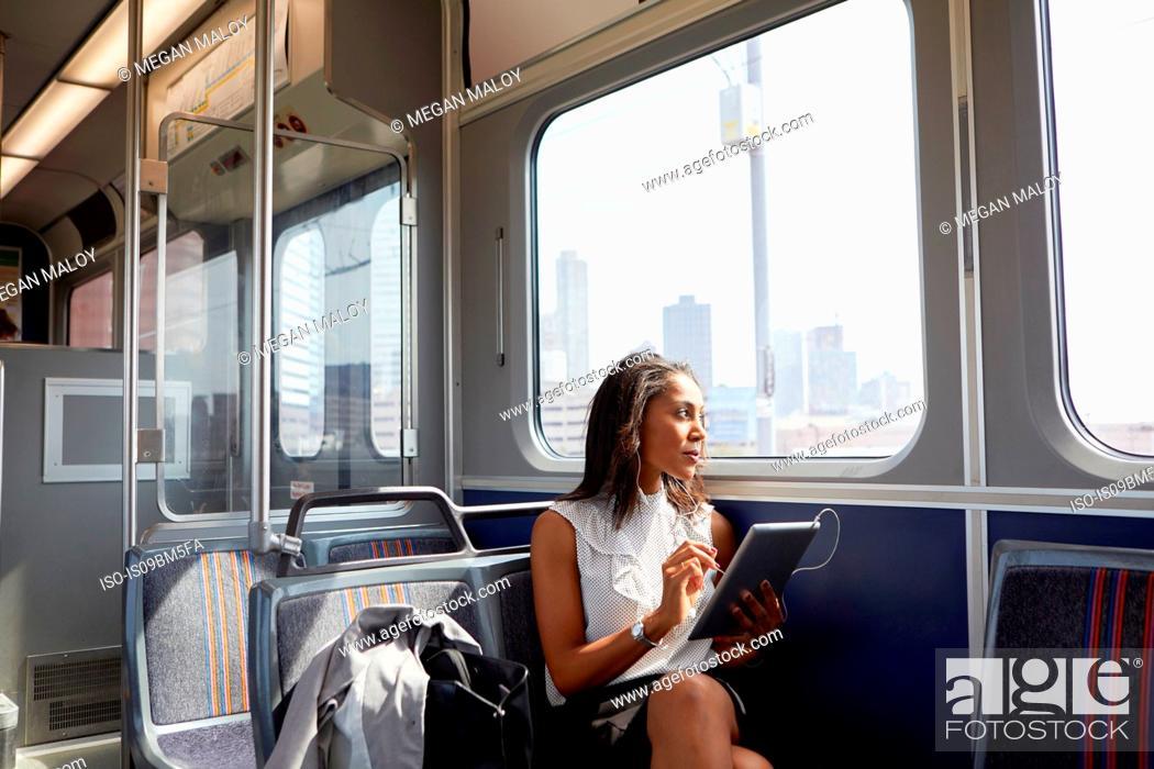 Stock Photo: Businesswoman using digital tablet on train.