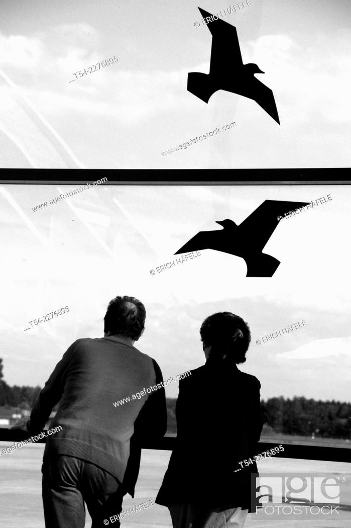 Stock Photo: Two people watch to the Birds at Allgaeu Airport, Memmingen, Germany.