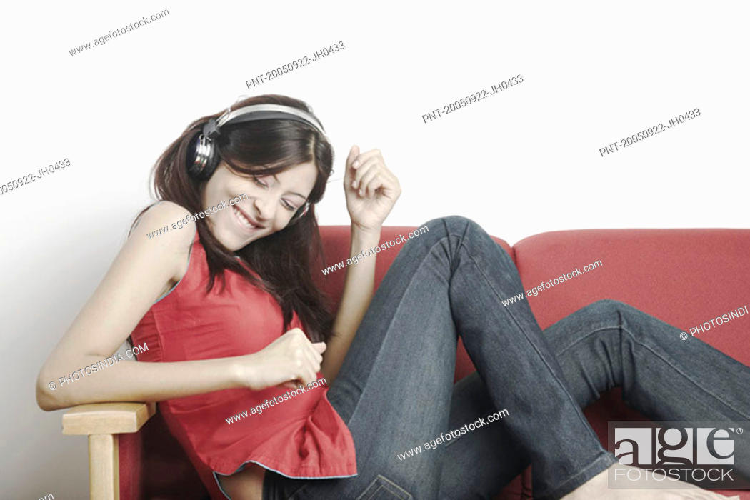 Stock Photo: Young woman sitting on a couch wearing headphones and listening to music.