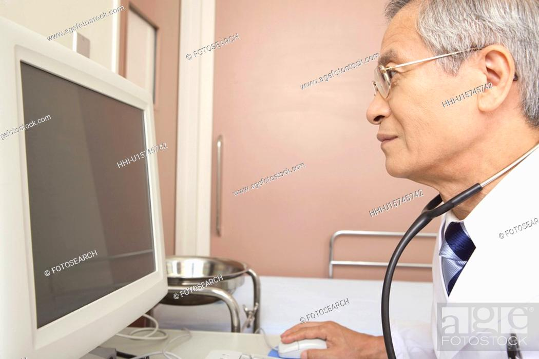 Stock Photo: Physician watching a monitor.