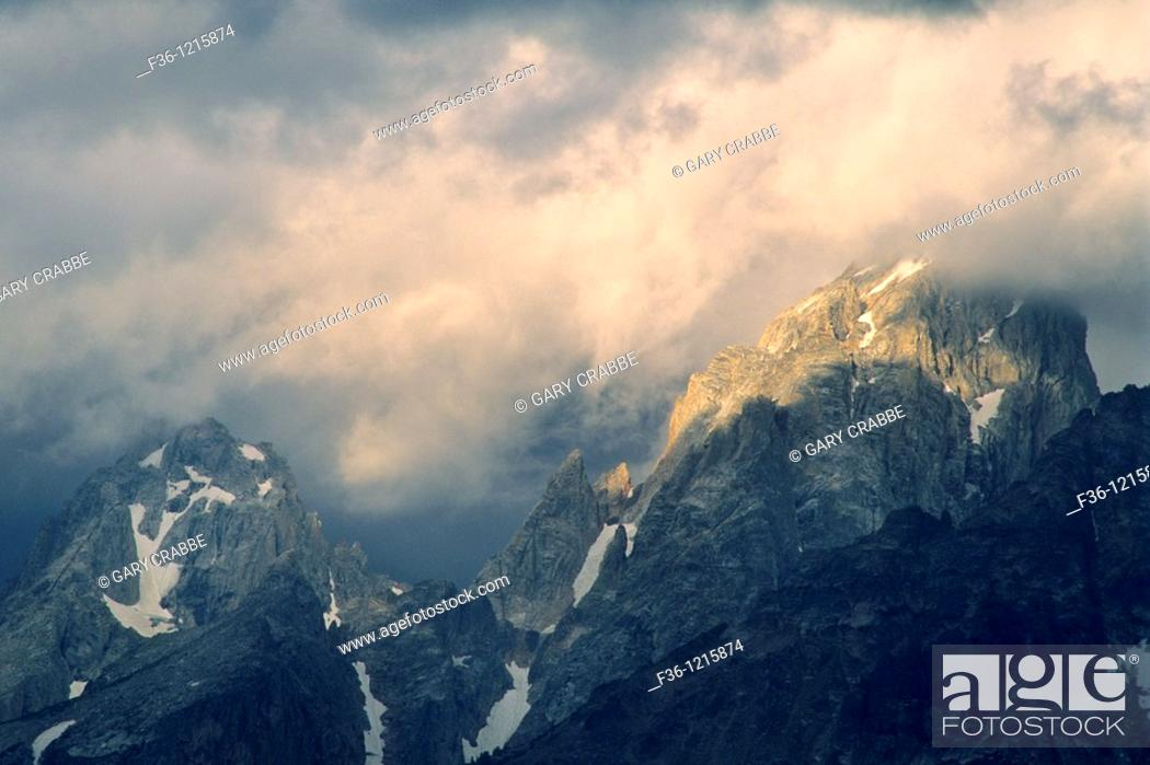 Stock Photo: Sunlight on storm clouds near the summit of the Grand Tetons, Grand Teton Nat'l  Pk , WYOMING.