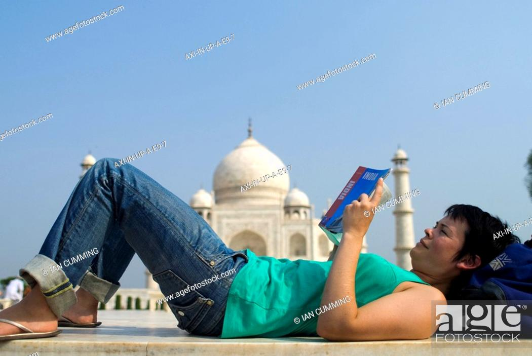 Stock Photo: Woman reading guide book in front of the Taj Mahal, Side View.