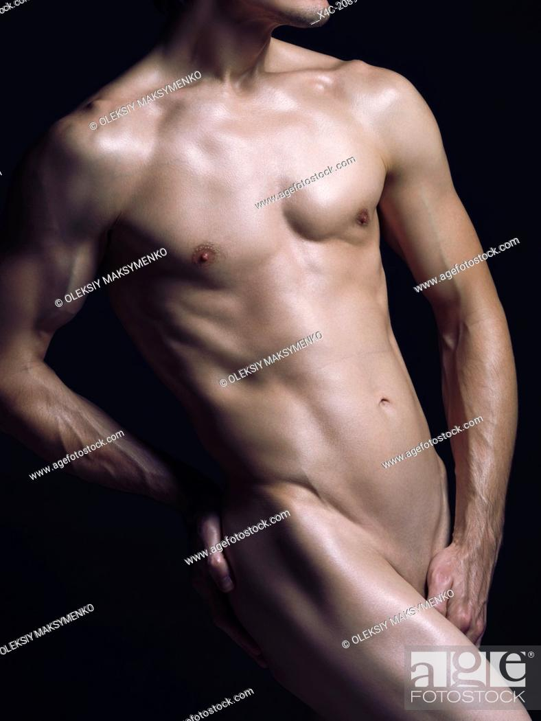 Stock Photo: Young nude man with fit shiny naked body isolated on black background.