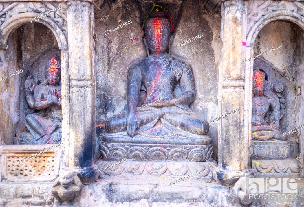 Stock Photo: Statue of Budda along side with Hindu Gods and Goddesses carved in a stone. Selective Focus.