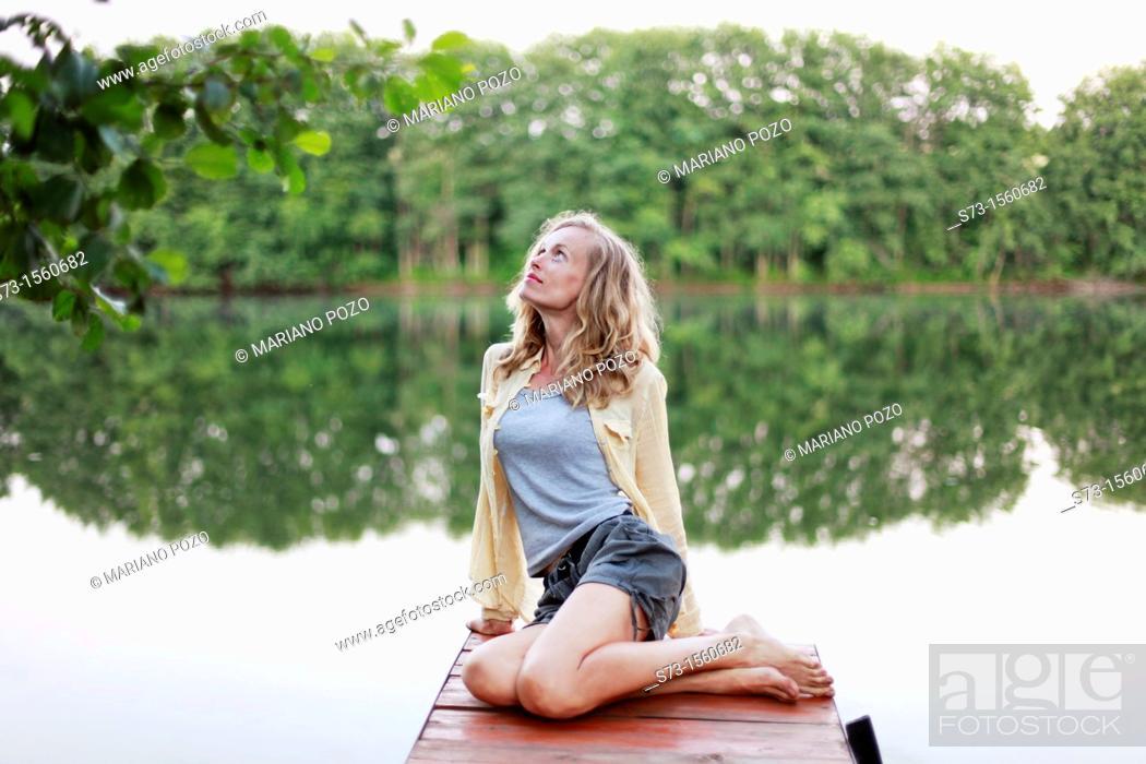 Stock Photo: Woman on the pier in Lake Avral, Kirillovka, Samara Region, Russian Federation.