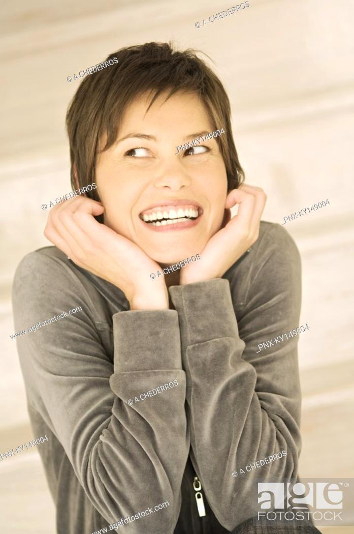 Stock Photo: Portrait of young smiling woman, looking away, hands on chin.