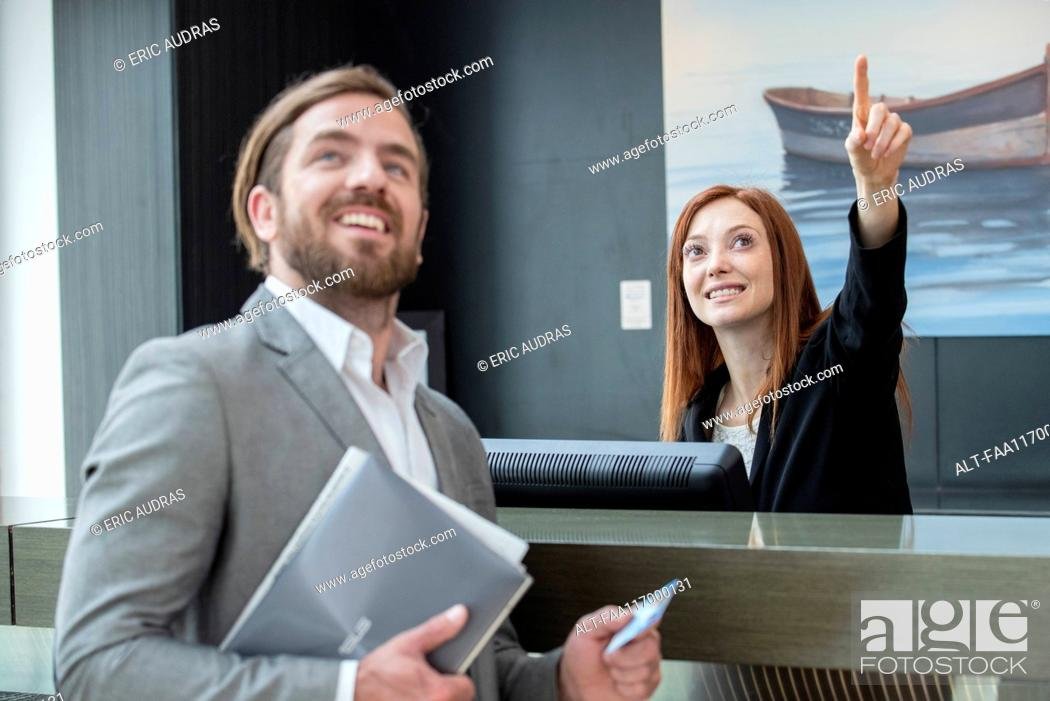 Photo de stock: Female receptionist showing room to businessman.