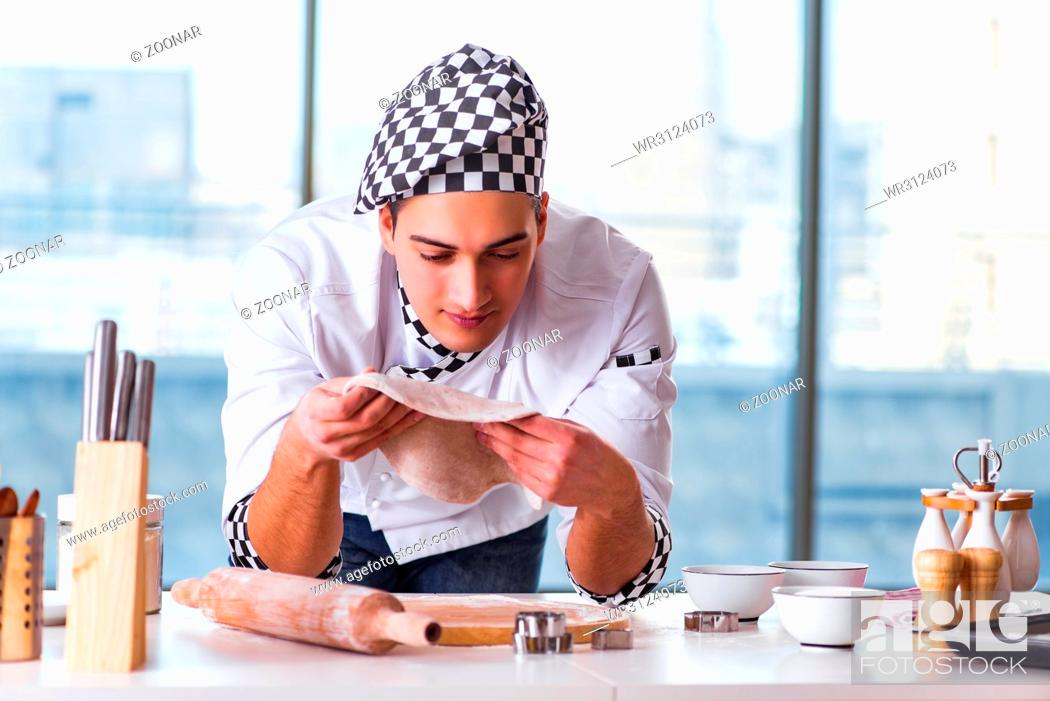 Stock Photo: Young man cooking cookies in kitchen.