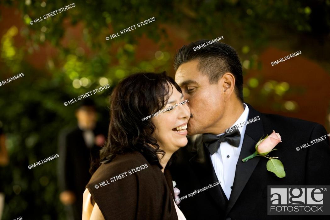 Stock Photo: Hispanic man kissing wife on cheek.