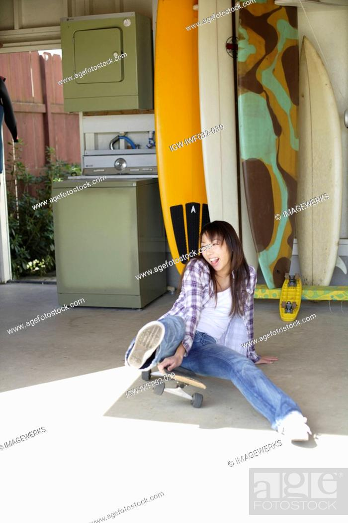 Stock Photo: View of a young woman sitting on the skateboard.