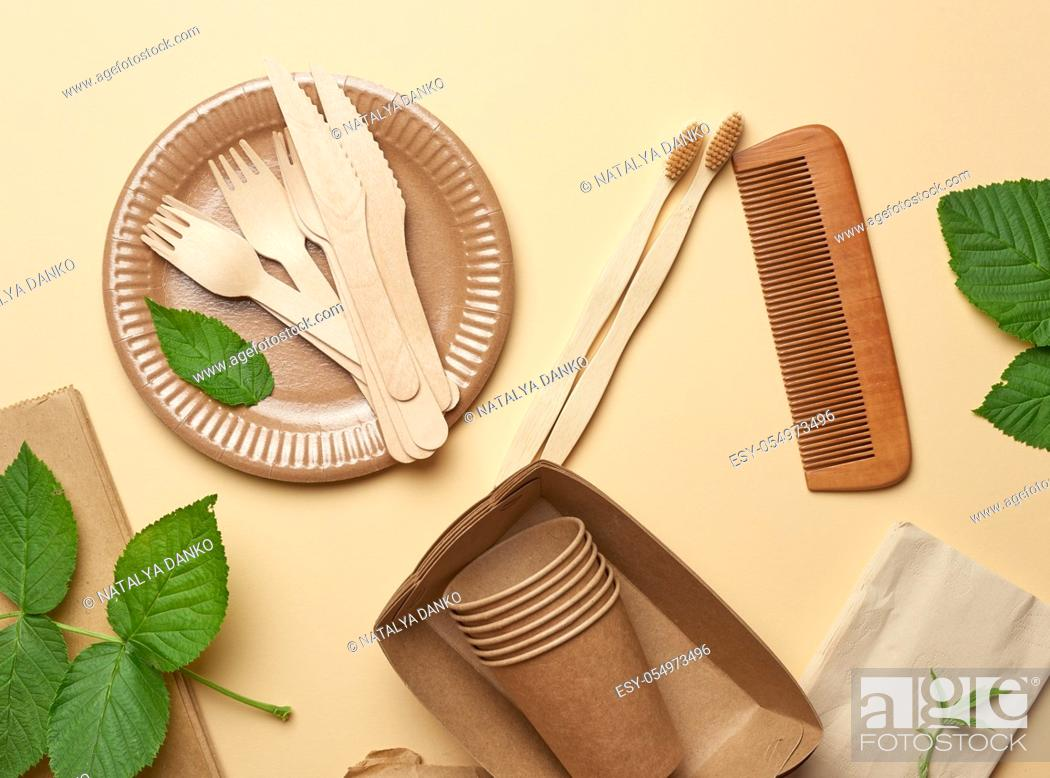 Stock Photo: paper plates and cups from brown craft paper and wooden forks and knive on a beige background. Plastic rejection concept, zero waste.
