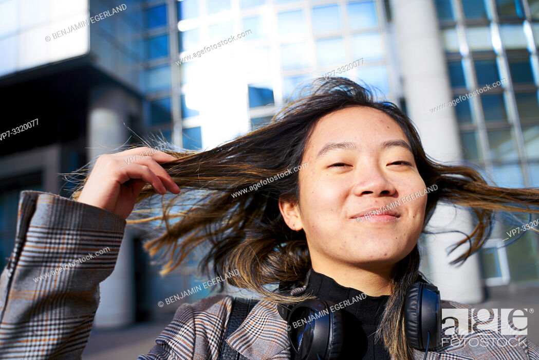 Photo de stock: young sanguine Asian woman playing with hairs, in business district in Paris, France.