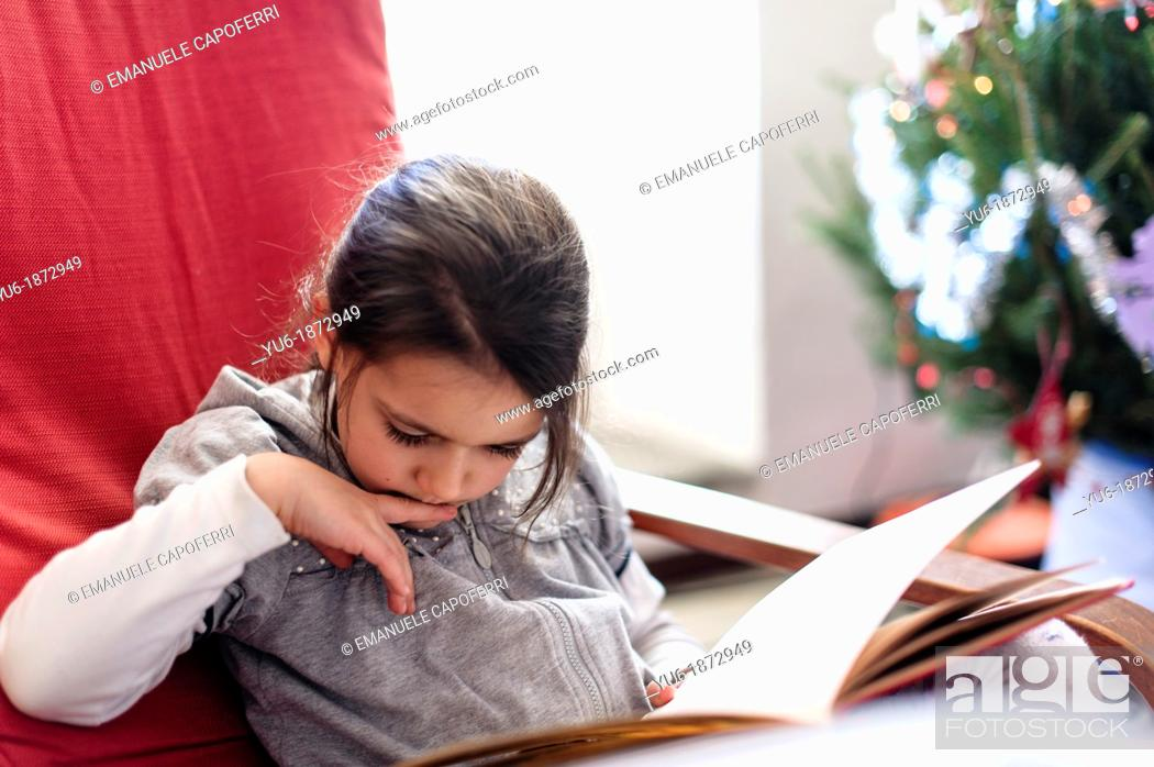 Stock Photo: Little girl reading a book sitting on red chair, next to the Christmas tree.