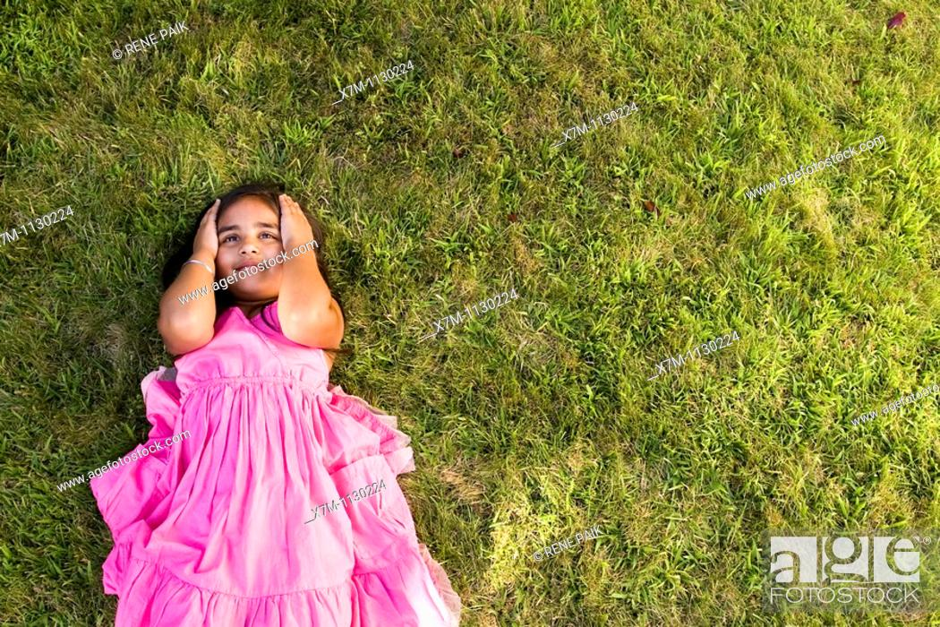 Stock Photo: A little Indian girl thinking while laying on green grass.