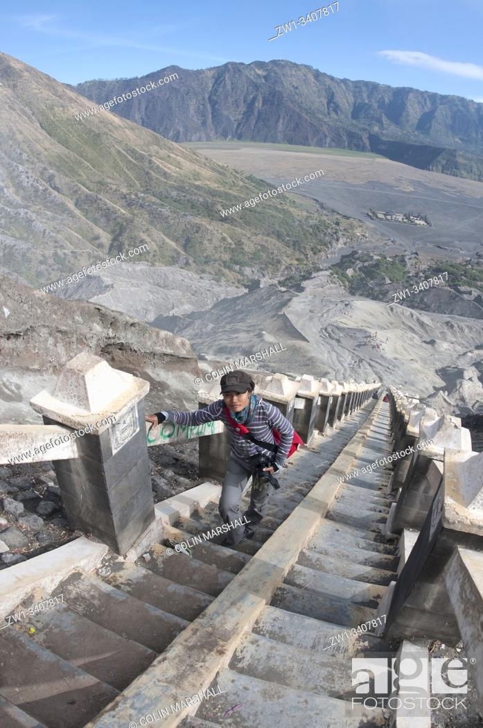 Stock Photo: Tourist (model released) walking up stairs to Mount Bromo with Sea of Sand in background, Bromo Tengger Semeru National Park, East Java, Indonesia.