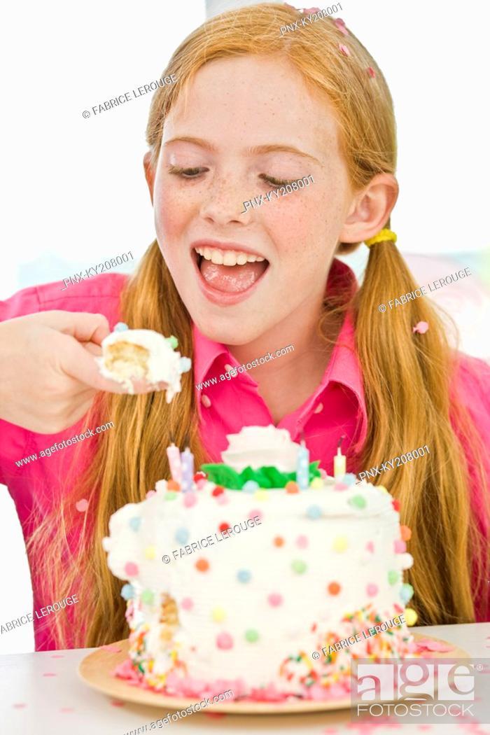 Stock Photo: Girl eating birthday cake.