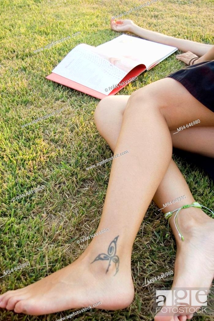 Stock Photo: Woman laying on grass reading a book.