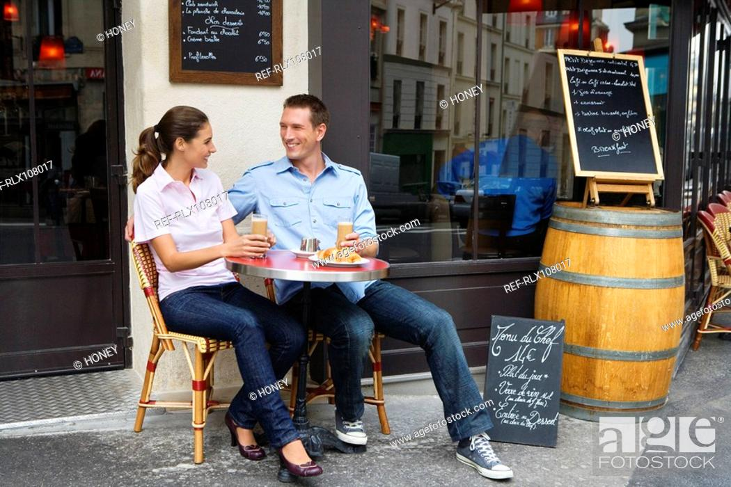 Stock Photo: Young couple sitting outside street side cafe, drinking coffee, Paris, France.
