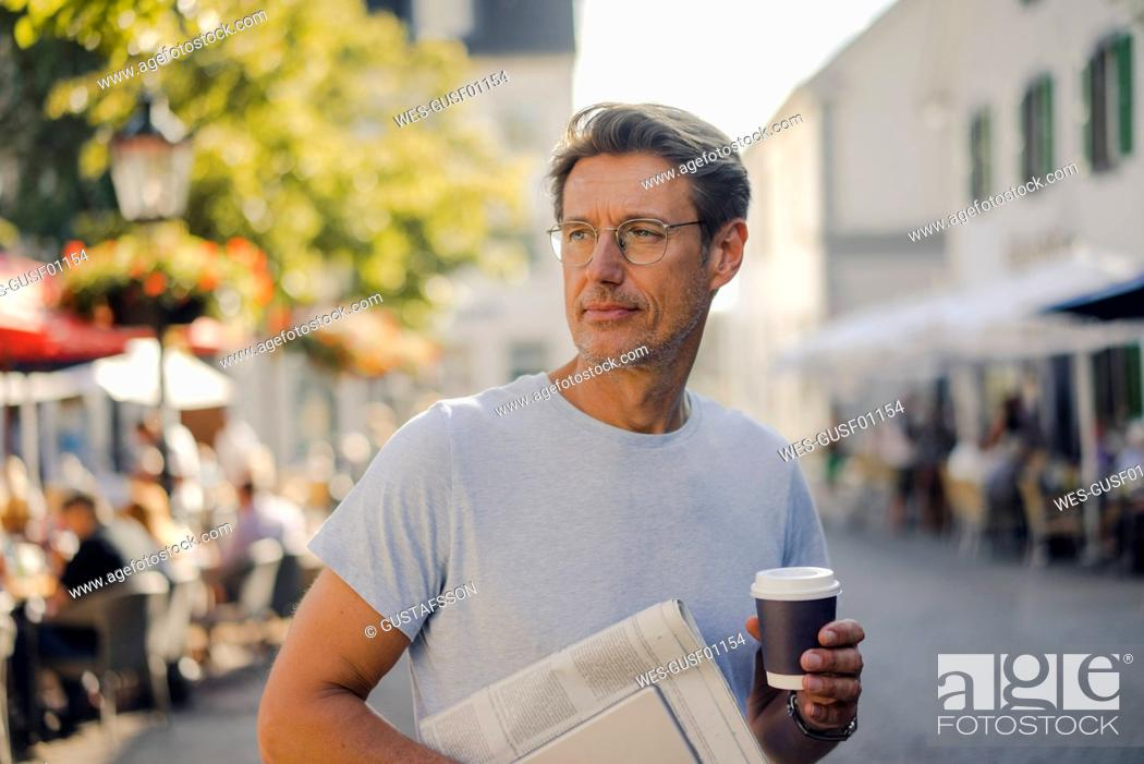 Stock Photo: Mature man walking in he city with newspaper and digital tablet, drinking coffee.
