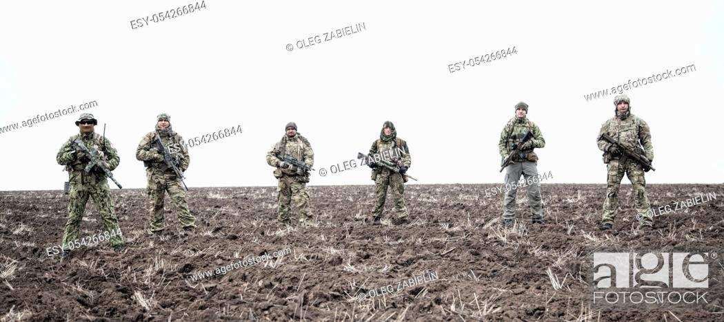Imagen: Army soldiers on march. Elite forces fighters group, commando tactical unit, reconnaissance team members in camouflage uniform, walking in line.