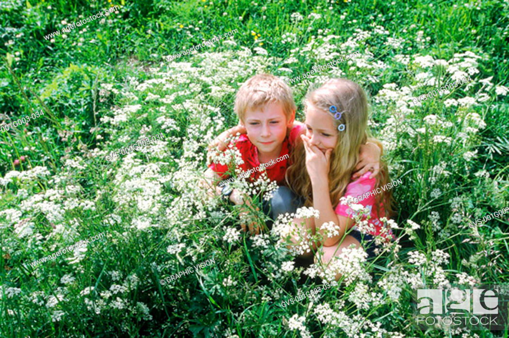 Stock Photo: Two young children squatting in a bush.