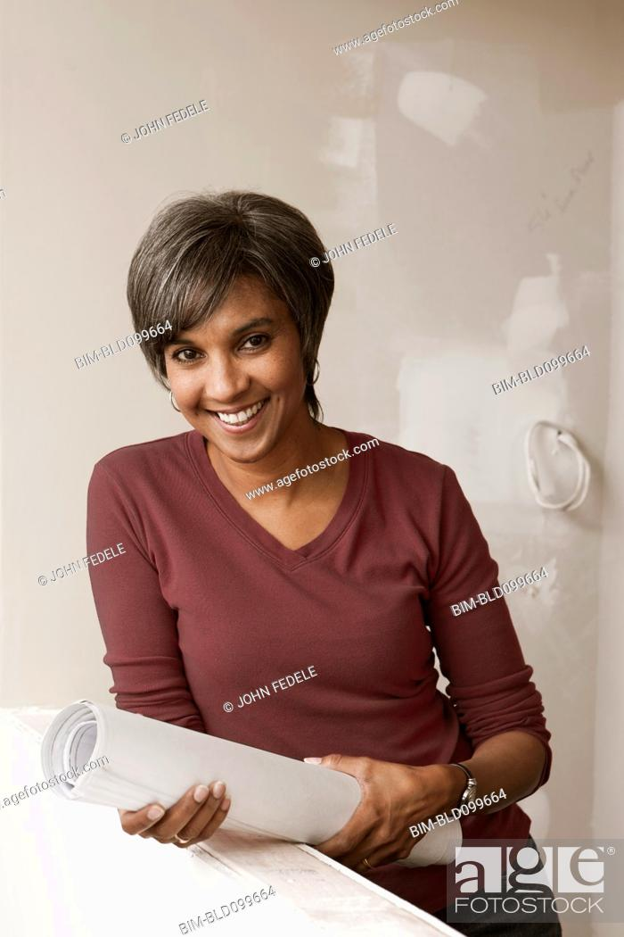 Stock Photo: Mixed race woman standing in unfinished room with blueprints.