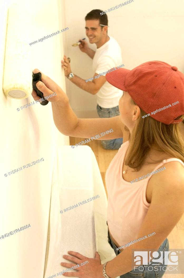 Stock Photo: Side profile of a young couple painting a wall.