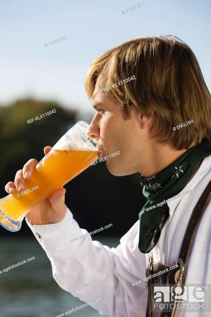 Stock Photo: Young man in traditional Bavarian outfit, drinking wheat beer, side profile.