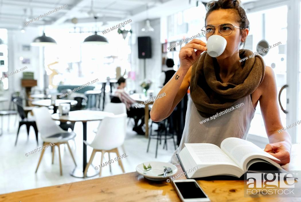 Stock Photo: Woman reading book in coffee shop drinking coffee.