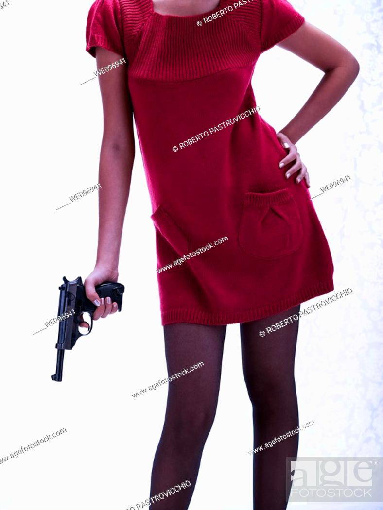 Stock Photo: Sexy girl in a red dress holding a dangerous gun.