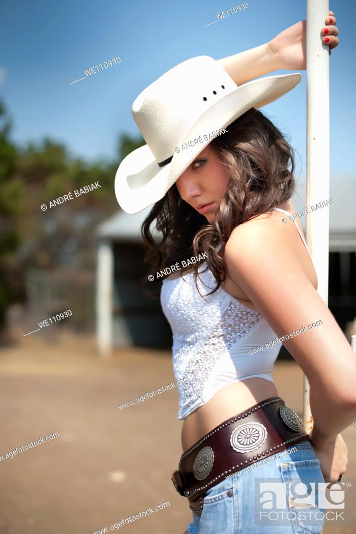 Stock Photo: Sexy cowgirl posing on a ranch.
