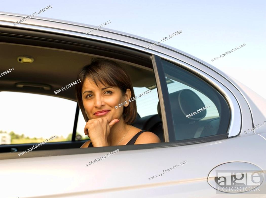 Stock Photo: Indian woman sitting in backseat of car.