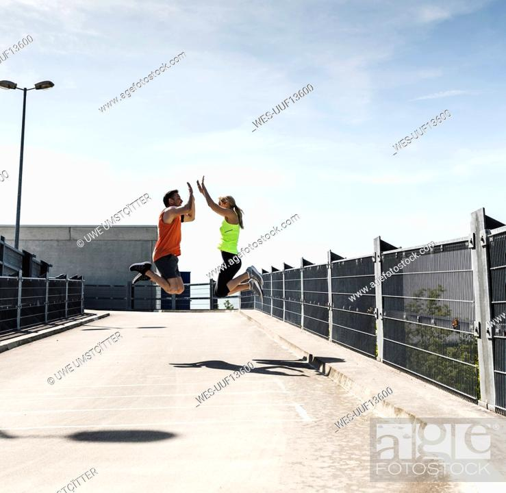 Stock Photo: Jogging couple jumping for joy, highfiving.