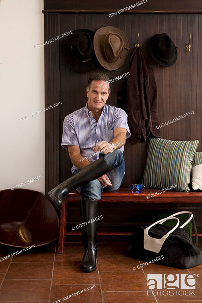 Stock Photo: Man wearing riding boots indoors.