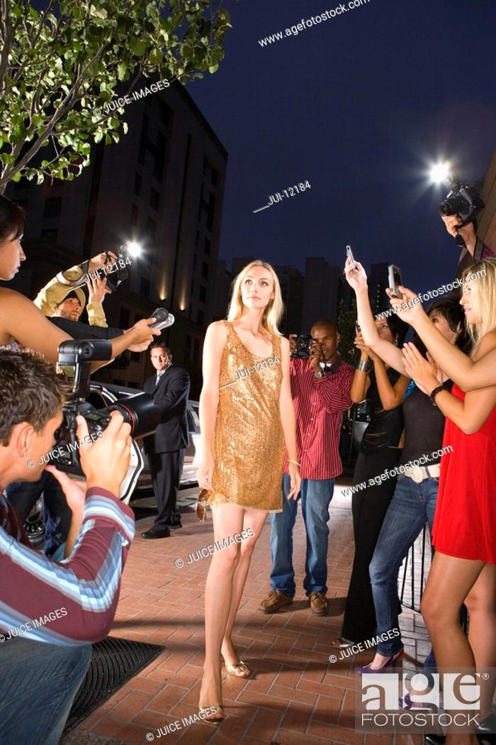 Stock Photo: Young woman surrounded in people taking photographs, low angle view.