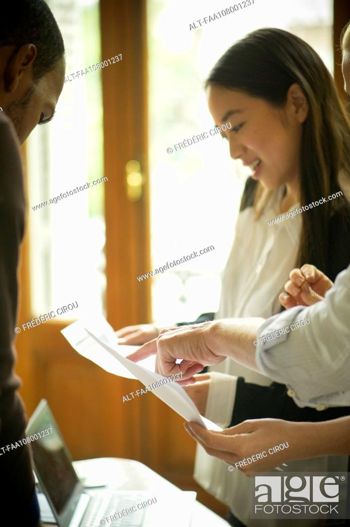 Stock Photo: Office workers discussing documents.