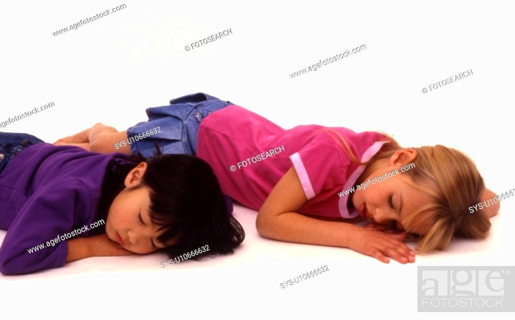 Stock Photo: Two girls sleeping on floor.