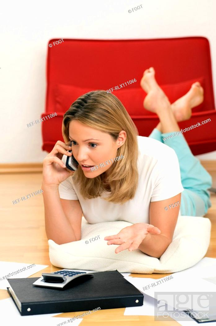 Stock Photo: Woman on phone doing home finances.