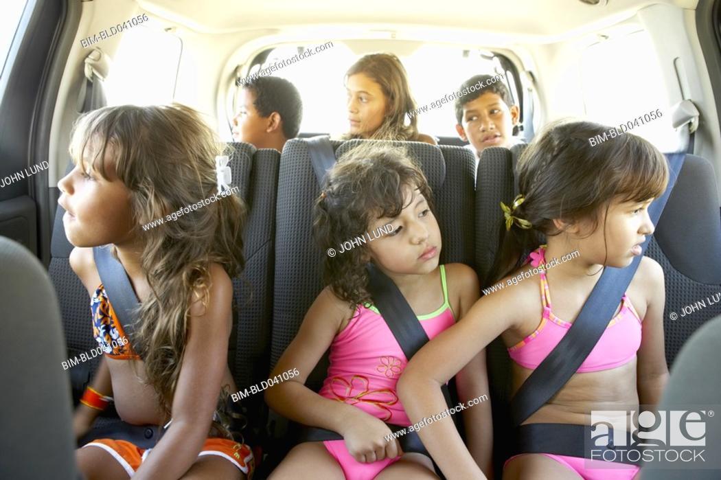 Stock Photo: Hispanic children in car wearing seatbelts.