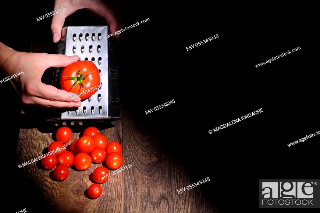 Stock Photo: Conceptual A Man Hands Grinds Tomato On A Grater.