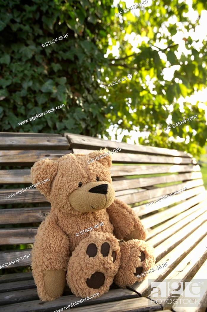 Stock Photo: Teddy bear on a wooden bench, selective focus.