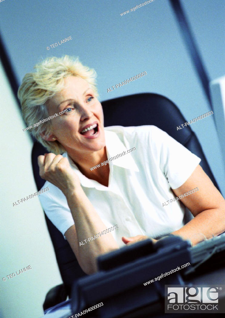 Stock Photo: Businesswoman raising fist and smiling.