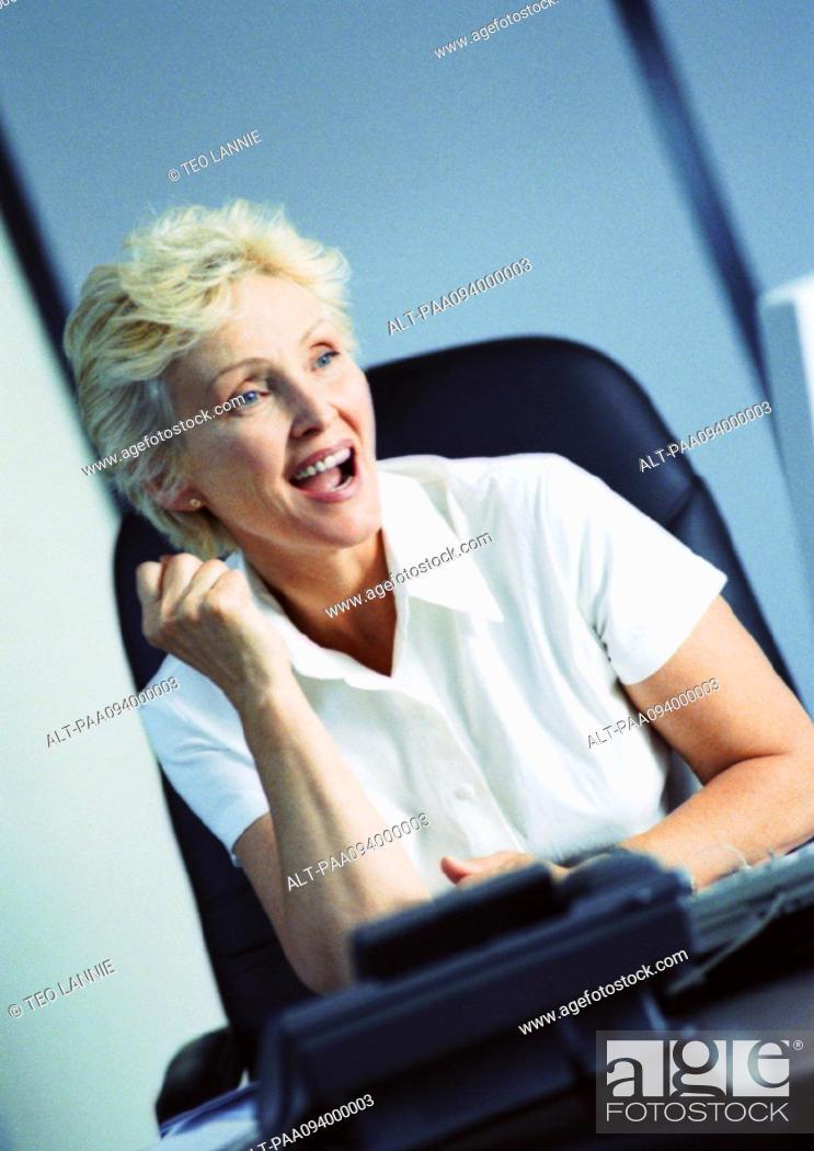 Stock Photo: Businesswoman raising fist and smiling.