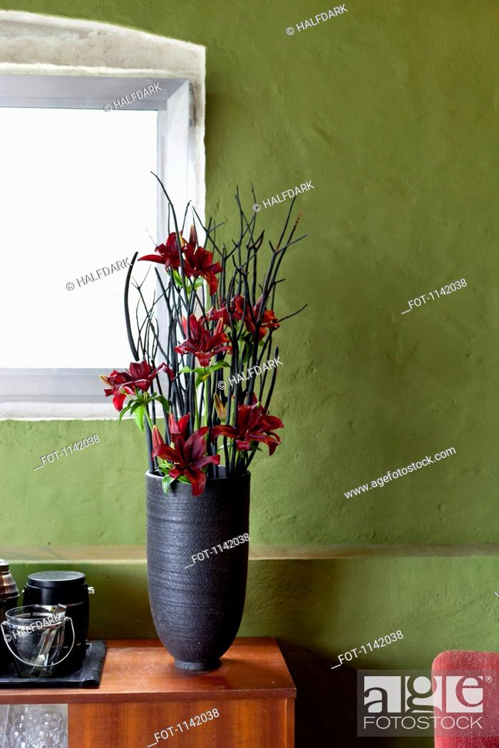 Stock Photo: A vase of flowers on a sideboard.
