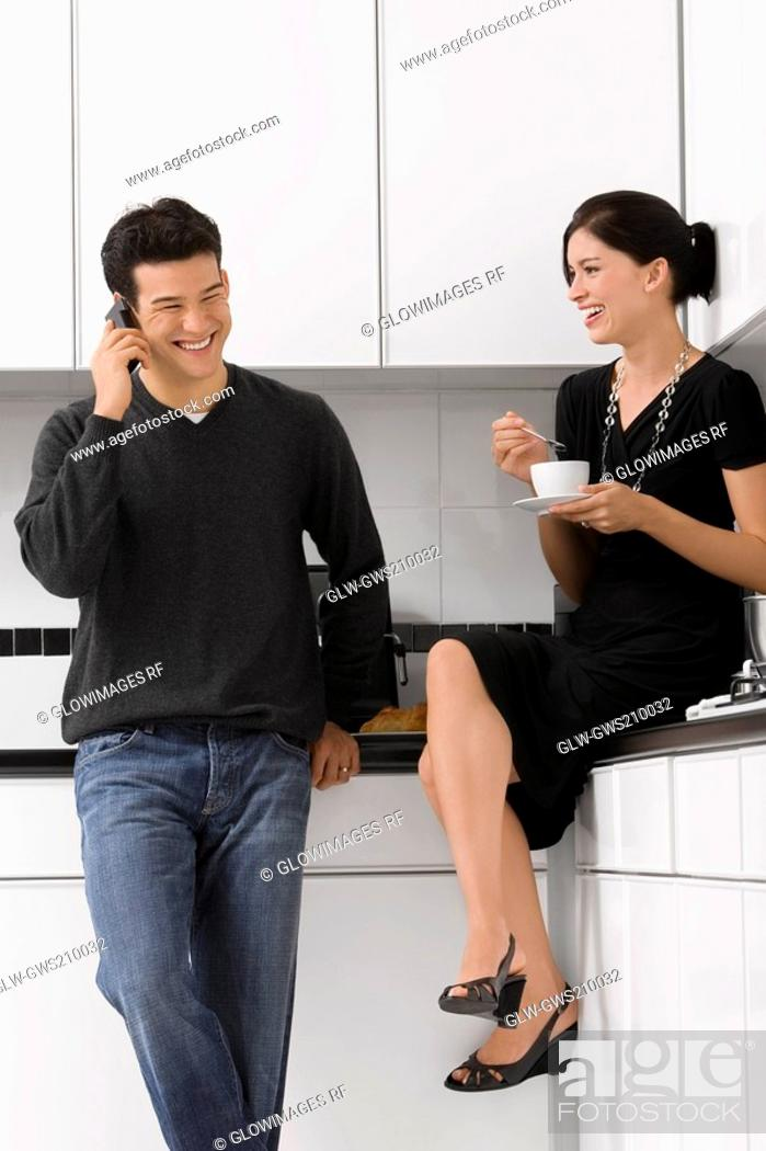 Stock Photo: Young woman holding a tea cup with a young man talking on a mobile phone.