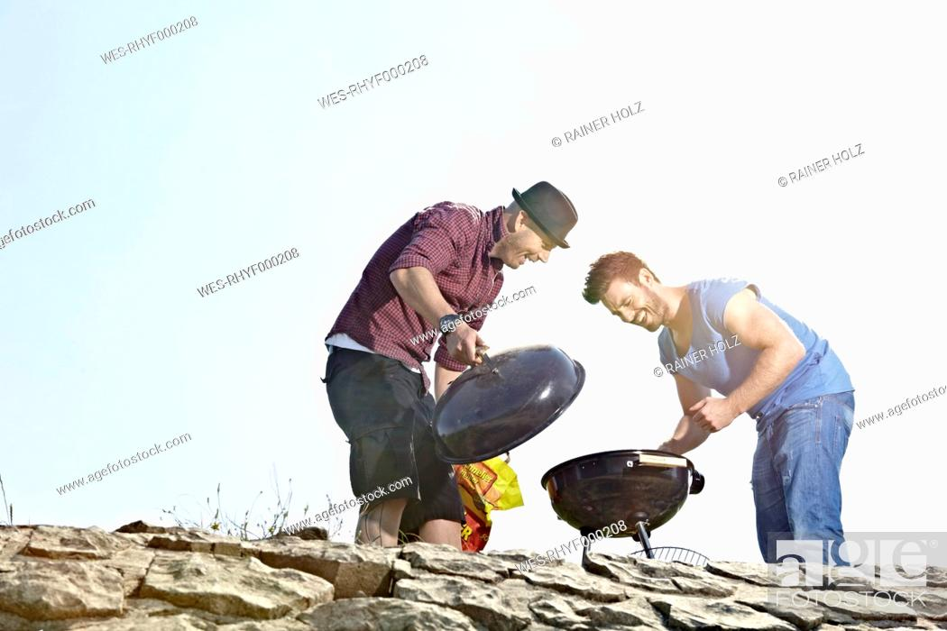 Stock Photo: Germany, Cologne, Men setting up grill.