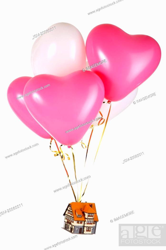 Stock Photo: A toy house flying with balloons.