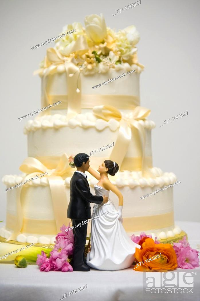 Stock Photo: Dolls representing a bride and a groom stand in front of a wedding cake.
