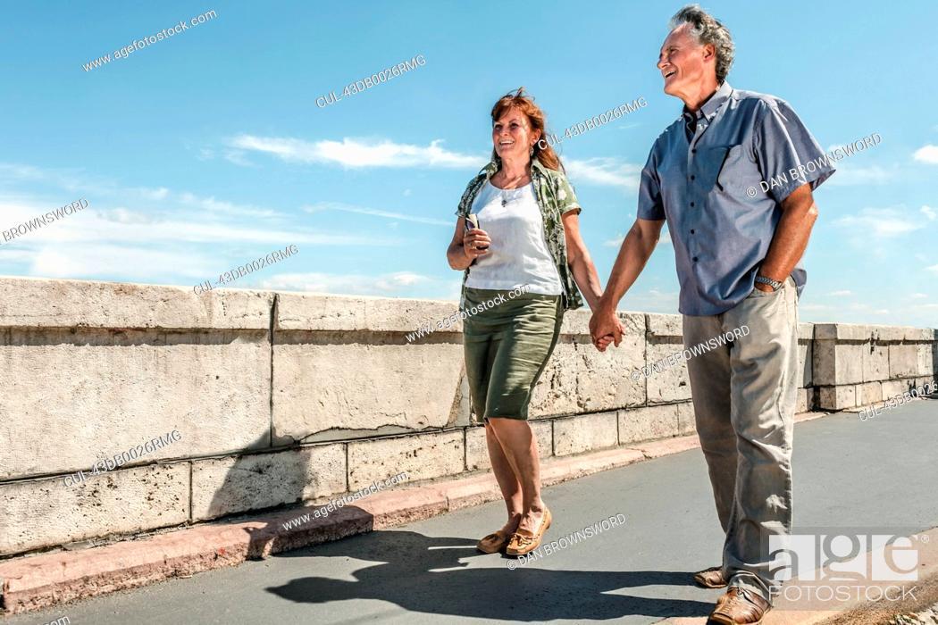 Stock Photo: Older couple holding hands on bridge.