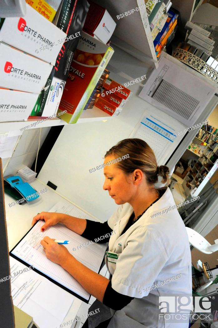Stock Photo: Reportage in a pharmacy in Auxi-le-Château, France. A pharmacy technician fills in the prescription book.